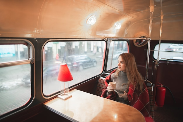 Young attractive woman sitting at the table in the bus cafe is covered with a blanket, holds a cup of coffee in her hands and looks in the window