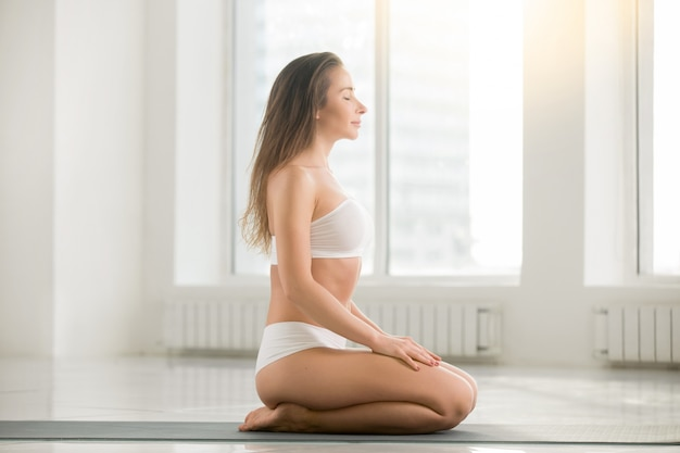 Young attractive woman sitting in vajrasana pose, white color ba