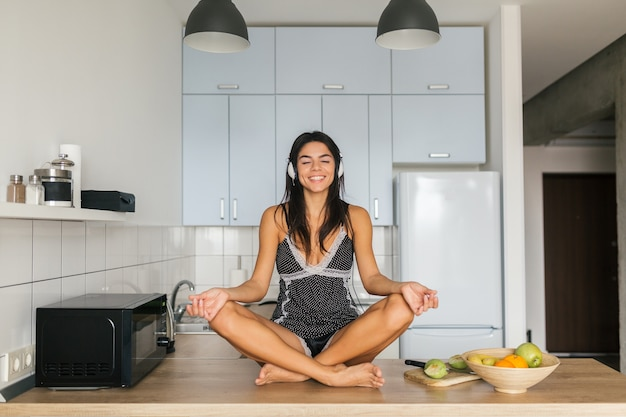 Young attractive woman sitting yoga asana pose in kitchen in morning, maditating, smiling, happy, positive, healthy lifestyle, listening to music on headphones, relaxation, harmony