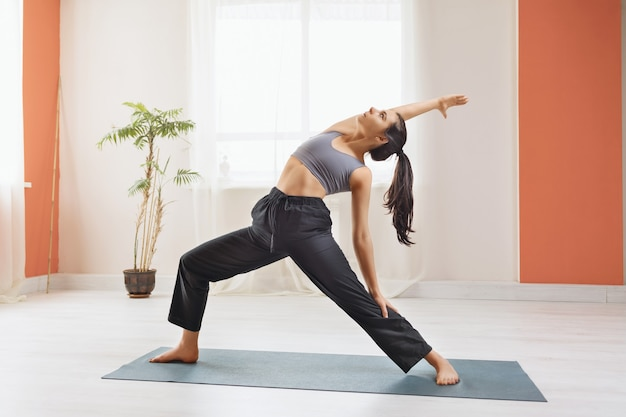 Young attractive woman in sportswear practicing yoga performs in the studio standing on the mat virabhadrasana exercise warrior pose