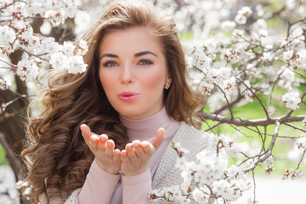 Young attractive woman on spring background with flowers. close up portrait of beautiful girl make up. lady outdoors in the garden