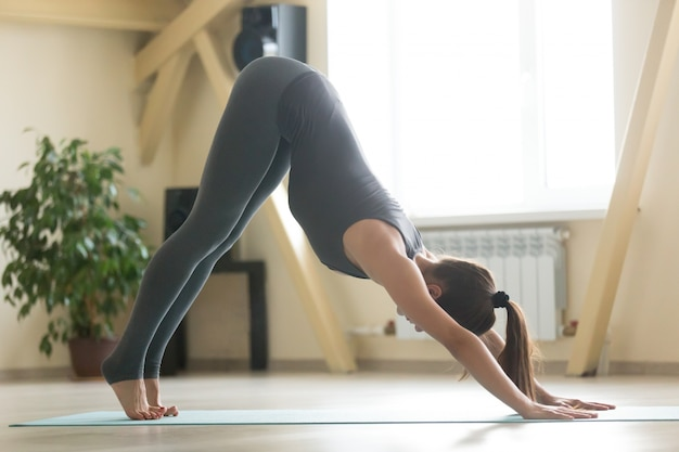 Young attractive woman standing in adho mukha svanasana pose, ho