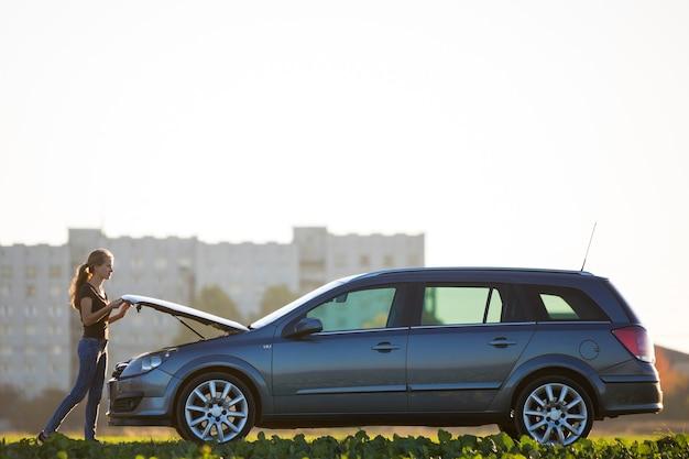 맑은 하늘 복사 공간 배경에 터진 후드 아래를 보고 은색 차에 서 있는 젊은 매력적인 여자. 교통, 차량 문제 및 고장 개념.