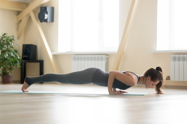 Young attractive woman standing in chaturanga dandasana pose, ho