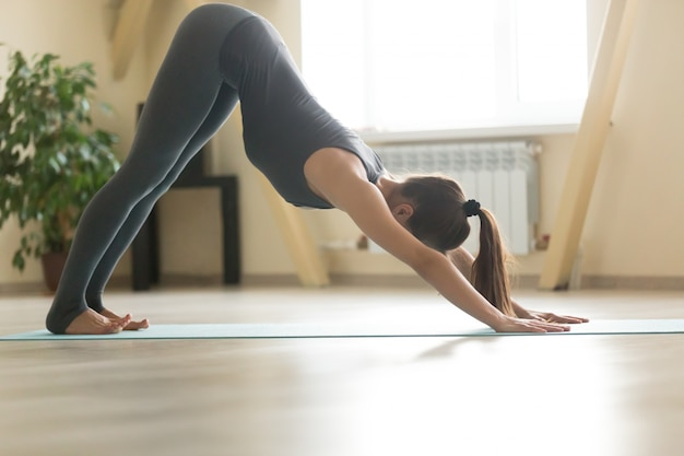 Young attractive woman standing in downward facing dog pose, hom