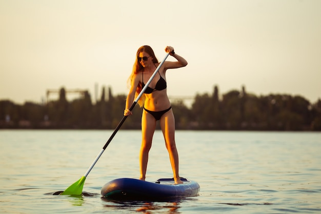 パドルボード、supに立っている若い魅力的な女性。アクティブな生活、スポーツ、レジャー活動の概念