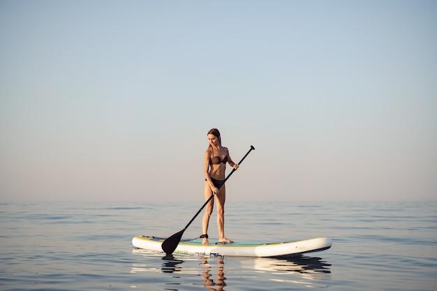 Молодая привлекательная женщина, стоящая на доске весла