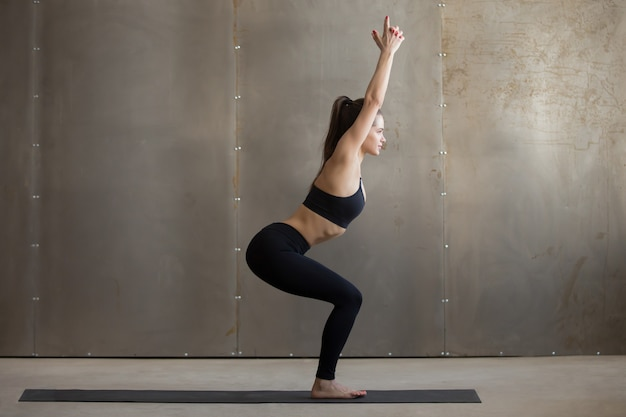 Young attractive woman standing in utkatasana pose, grey studio
