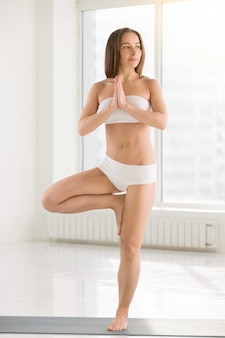 Young attractive woman standing in vrksasana pose, white color b