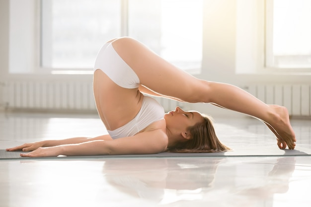 Young attractive woman stretching in plough pose, white color ba