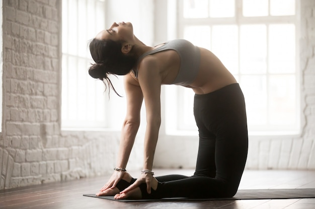 Young attractive woman stretching in ustrasana pose, white loft