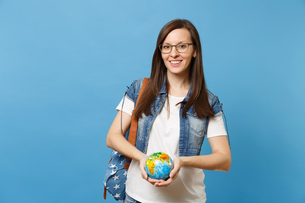 파란색 배경에 고립 된 세계 글로브를 들고 배낭 데님 옷 안경에 젊은 매력적인 여자 학생. 고등학교에서 교육입니다. 행성을 저장합니다. 생태 환경 보호 개념입니다.