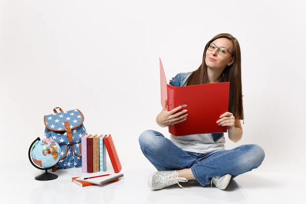 Молодая привлекательная студентка в очках, держащая красную папку для документов, документов, сидящих рядом с рюкзаком с глобусом, изолированные школьные учебники