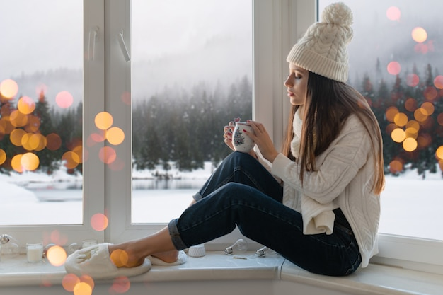 Young attractive woman in stylish white knitted sweater, scarf and hat sitting at home on windowsill at christmas holding cup drinking hot tea, winter forest background view, lights bokeh