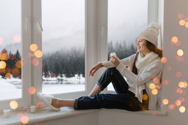Young attractive woman in stylish white knitted sweater, scarf and hat sitting at home on windowsill at christmas holding glass snow ball present decoration, winter forest view, lights bokeh