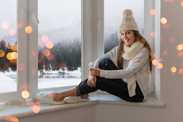 Giovane donna attraente in elegante maglione lavorato a maglia bianco, sciarpa e cappello seduto a casa sul davanzale della finestra a natale che tiene la decorazione presente della palla di neve di vetro, vista della foresta di inverno, bokeh delle luci