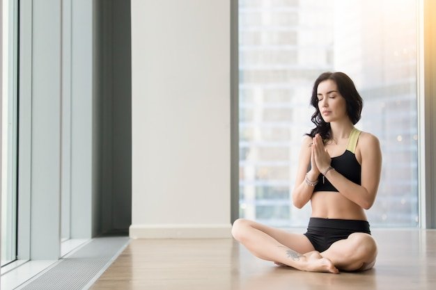 Young attractive woman in sukhasana pose near the floor windows