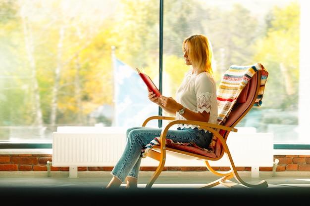 Молодая привлекательная женщина качается в удобном кресле-качалке, читая свою любимую книгу. хорошее времяпровождение. фотография с пустым боковым пространством.