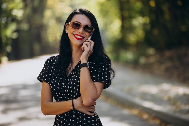 Молодая привлекательная женщина разговаривает по телефону в парке