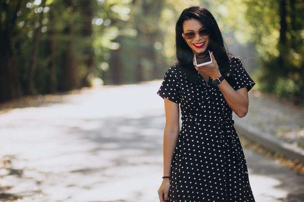 公園で電話で話している若い魅力的な女性