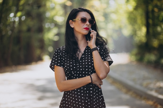 Young attractive woman talking on the phone in park