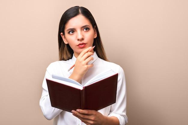 Молодая привлекательная женщина думая держащ ее подбородок и тетрадь и ручку. ищу правильный ответ