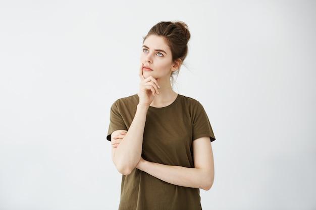 Giovane donna attraente che pensa con la mano sul mento che guarda alla distanza.