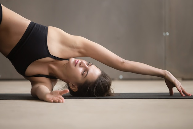 Young attractive woman in thread the needle pose, closeup, studi