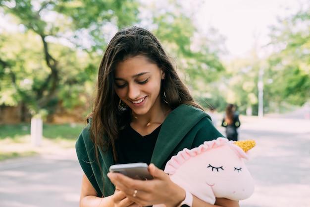 Giovane donna attraente digitando messaggi sul suo cellulare.