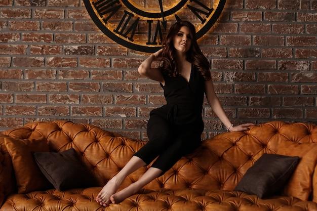 벽돌 벽에 시계에서 젊은 매력적인 여자