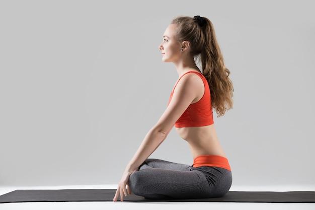 Young attractive woman in upward abdominal lock pose, grey studi