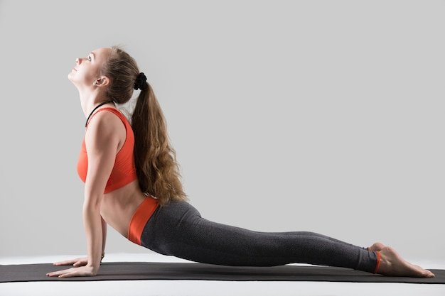 Young attractive woman in upward facing dog pose, grey studio