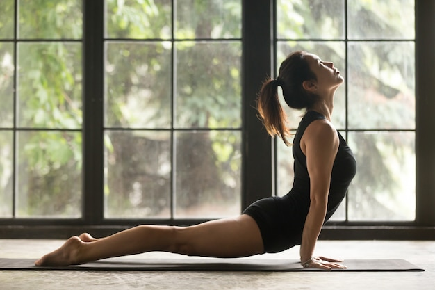 Young attractive woman in upward facing dog pose