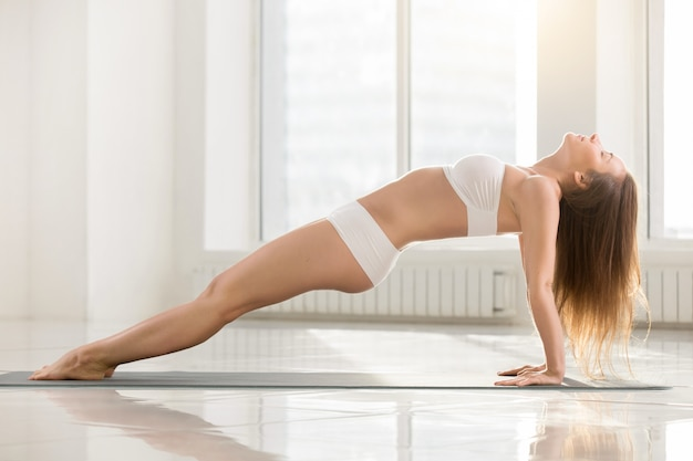 Young attractive woman in upward plank pose, white color backgro