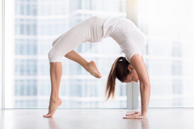 Young attractive woman in urdhva dhanurasana pose against floor window