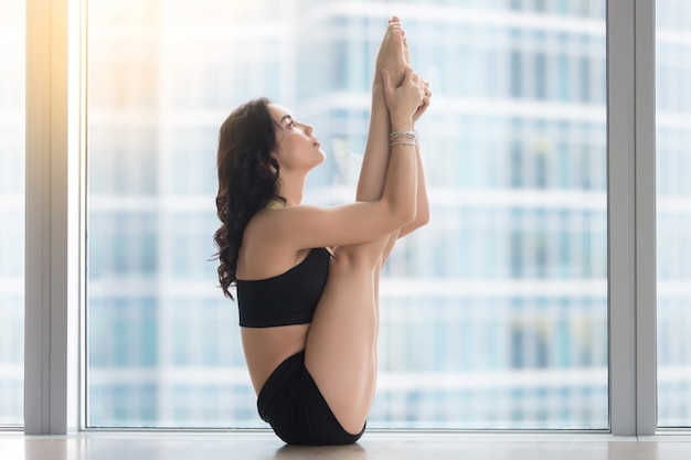 Young attractive woman in urdhva mukha paschimottanasana pose