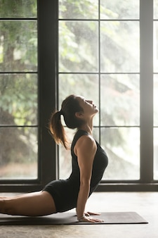 Young attractive woman in urdhva mukha svanasana pose