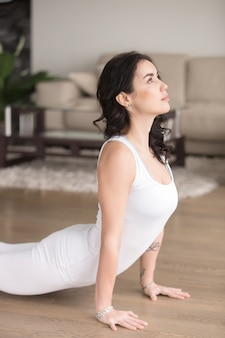 Young attractive woman in the urdhva mukha svanasana pose