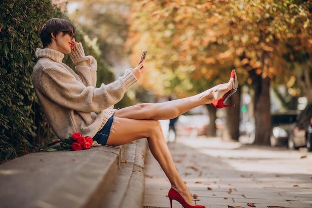 Молодая привлекательная женщина с помощью телефона