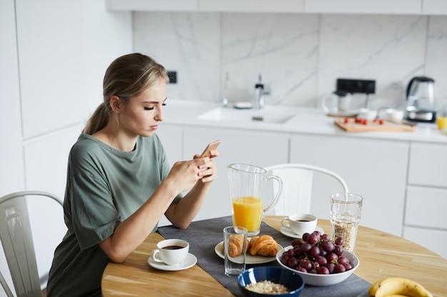 Молодая привлекательная женщина используя smartphone пока имеющ завтрак