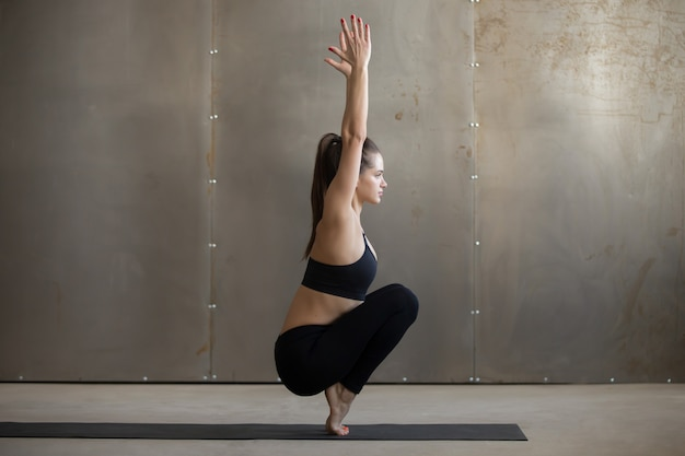 Young attractive woman in utkatasana pose, grey studio backgroun
