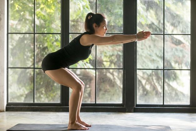 Young attractive woman in utkatasana pose, studio background