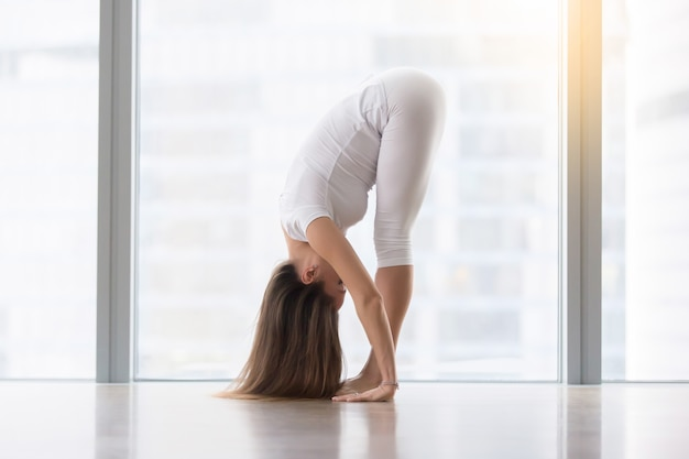 Young attractive woman in uttanasana pose against floor window