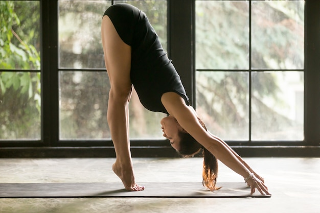 Young attractive woman in uttanasana pose, window background