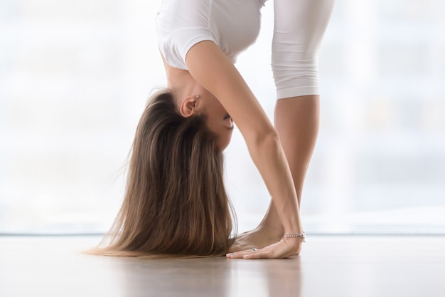 Young attractive woman in uttanasana pose