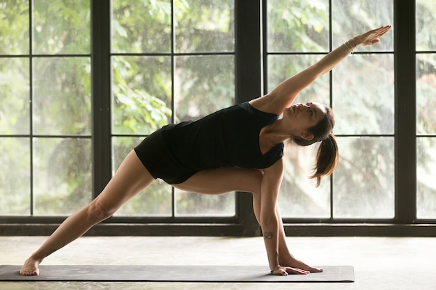Young attractive woman in utthita parsvakonasana pose