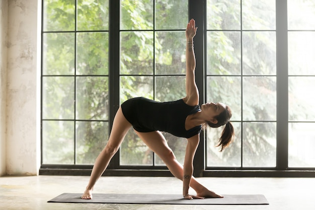 Young attractive woman in utthita trikonasana pose