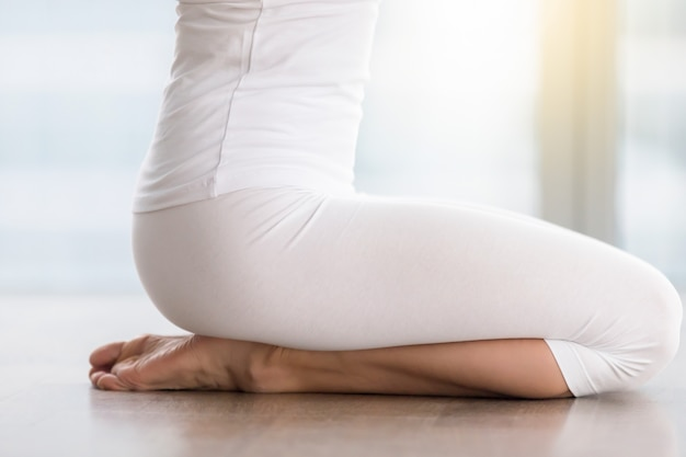 Young attractive woman in vajrasana pose, closeup of legs