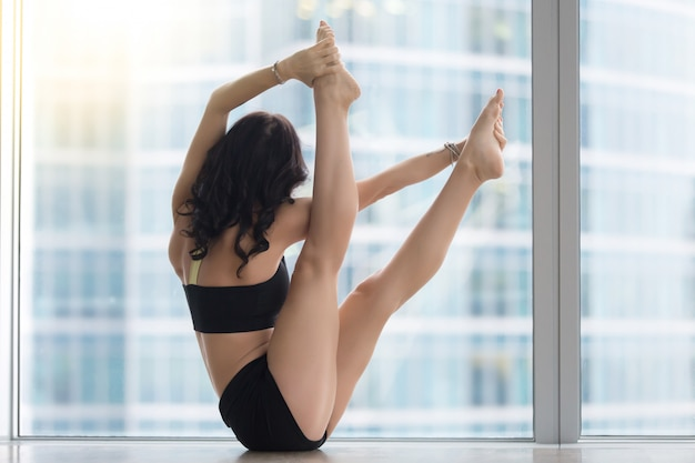 Young attractive woman in variation navasana pose against floor