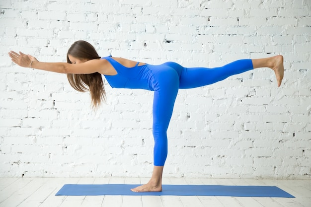 Young attractive woman in virabhadrasana iii pose, white studio
